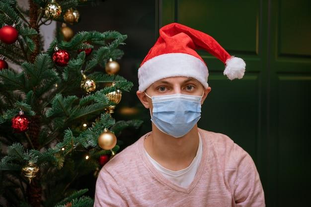 Junger mann zu hause in der nähe eines weihnachtsbaumes, der eine maske und einen weihnachtsmann-hut trägt, schaut in die kamera