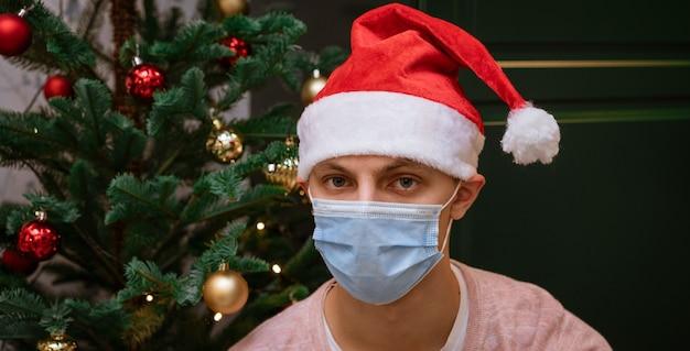 Junger mann zu hause in der nähe eines weihnachtsbaumes, der eine maske und einen weihnachtsmannhut trägt, schaut in die kamera