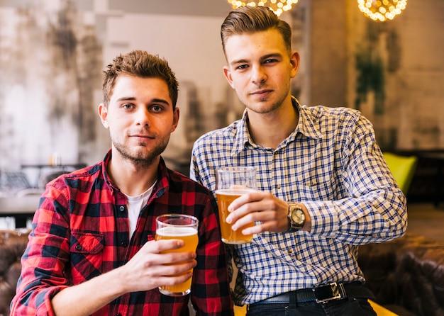 Junger mann zwei, der die gläser bier in der kneipe hält