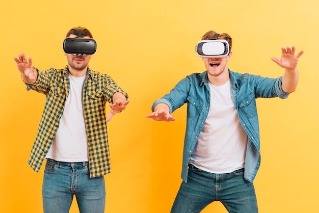 Junger mann zwei, der die schutzbrillen der virtuellen realität sich berühren in der luft gegen gelben hintergrund verwendet