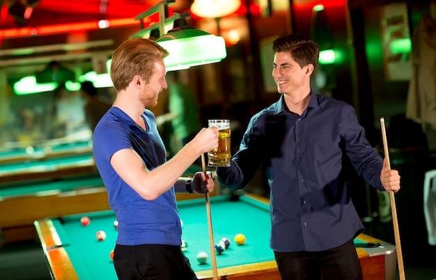Junger mann zwei, der mit einem bier röstet und poolstock in seinen händen hält