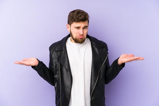 Junger mann zweifelt und zuckt mit den schultern in fragender geste.