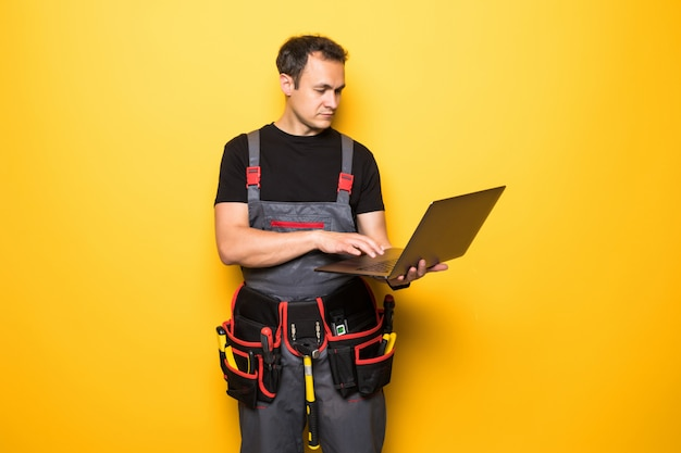 Junger mannarbeiter mit werkzeuggürtel mit laptop