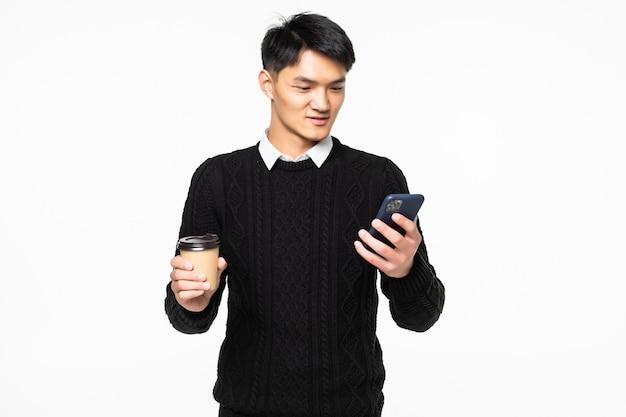 Junger manngebrauch auf handy mit kaffee auf weißer wand