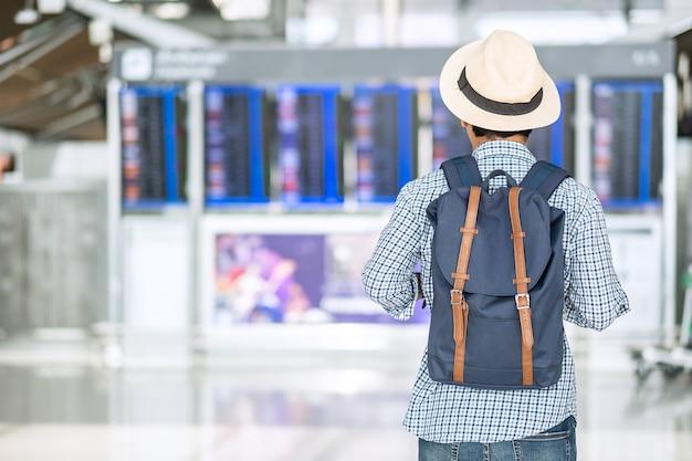 Junger mannreisender mit hipster-rucksack, der flugzeit prüft