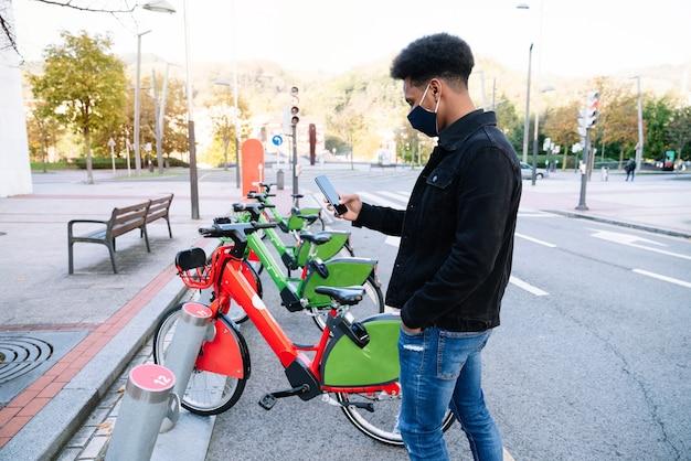 Junger marokkanischer junge, der sein handy benutzt, um ein gemietetes elektrofahrrad im straßenfahrradpark abzuholen, und eine gesichtsmaske zur coronavirus-pandemie trägt