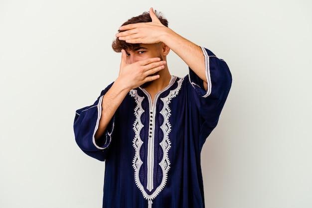 Junger marokkanischer mann blinzelt durch finger in die kamera, verlegenes bedeckendes gesicht.