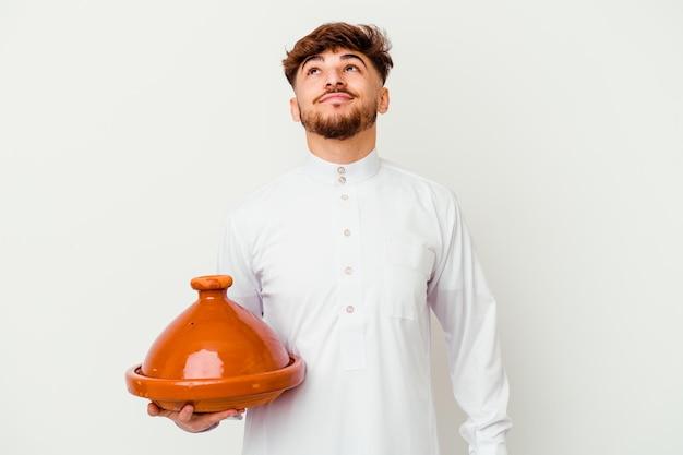 Junger marokkanischer mann, der das typische arabische kostüm hält, das eine tajine isoliert auf weiß träumt, ziele und zwecke zu erreichen