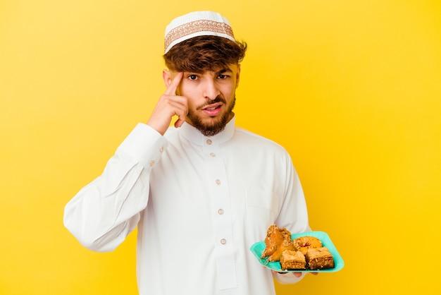 Junger marokkanischer mann, der das typische arabische kostüm isst, das arabische süßigkeiten isst, die auf gelb lokalisiert werden und eine enttäuschungsgeste mit zeigefinger zeigen.