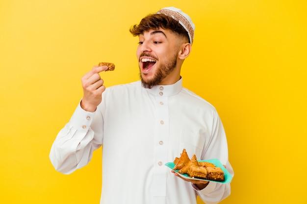 Junger marokkanischer mann, der das typische arabische kostüm isst, das arabische süßigkeiten isst, die auf gelber wand lokalisiert werden