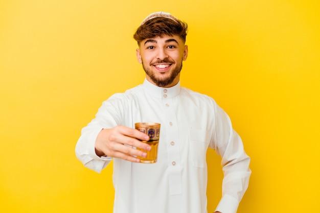 Junger marokkanischer mann, der das typische arabische kostüm trägt, das tee trinkt, der auf gelber wand lokalisiert wird