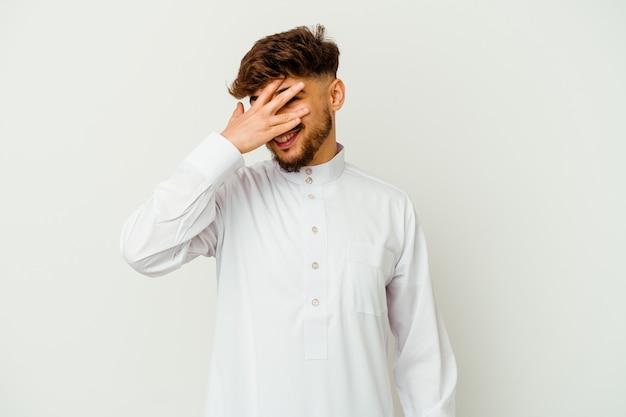 Junger marokkanischer mann, der eine typische arabische kleidung trägt, blinzelt in die kamera durch finger, verlegenes bedeckendes gesicht.