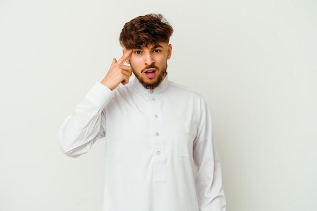 Junger marokkanischer mann, der eine typische arabische kleidung trägt, die auf weiß lokalisiert wird und eine enttäuschungsgeste mit zeigefinger zeigt.