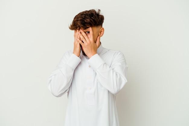 Junger marokkanischer mann, der eine typische arabische kleidung trägt, die auf weißem hintergrund isoliert ist, blinzelt durch erschrockene und nervöse finger.