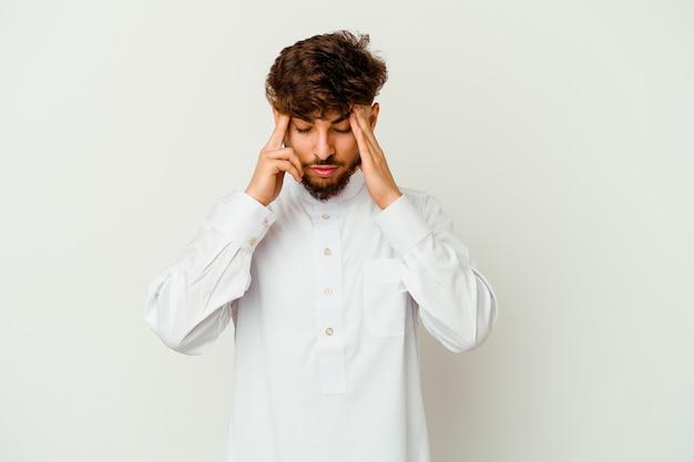 Junger marokkanischer mann, der eine typische arabische kleidung trägt, die auf weißen berührenden schläfen isoliert ist und kopfschmerzen hat.