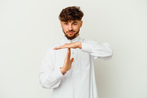Junger marokkanischer mann, der eine typische arabische kleidung trägt, die auf weißer wand lokalisiert wird, die eine zeitüberschreitungsgeste zeigt.