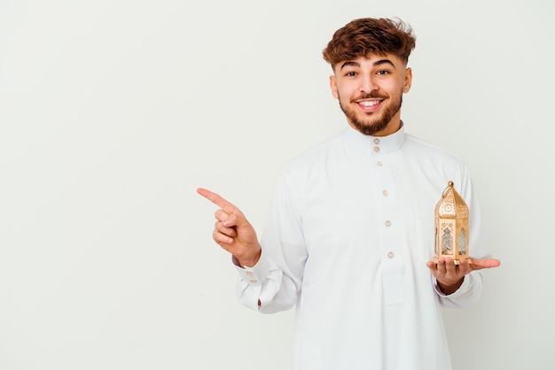 Junger marokkanischer mann, der eine typische arabische kleidung trägt, die eine ramadanlampe hält, die auf weißem lächeln lokalisiert und zur seite zeigt und etwas an der leeren stelle zeigt.