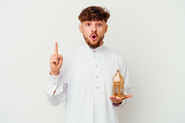 Junger marokkanischer mann, der eine typische arabische kleidung trägt, die eine ramadanlampe lokalisiert auf weiß hält, die eine große idee, konzept der kreativität hat.