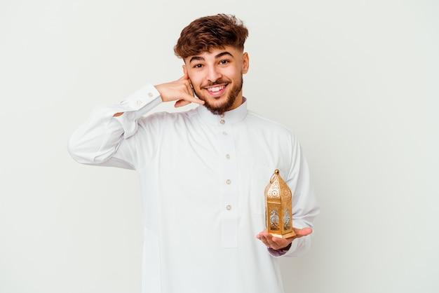 Junger marokkanischer mann, der eine typische arabische kleidung trägt, die eine ramadanlampe lokalisiert auf weiß hält, die eine handy-anrufgeste mit den fingern zeigt.