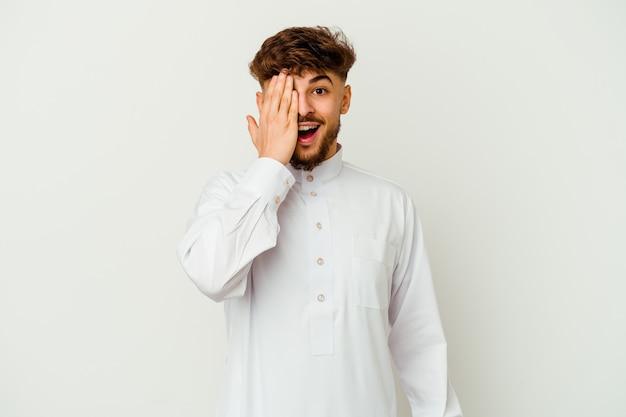 Junger marokkanischer mann, der eine typische arabische kleidung trägt, die spaß hat, die hälfte des gesichts mit handfläche bedeckend.