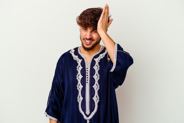 Junger marokkanischer mann, der etwas vergisst, mit der handfläche auf die stirn schlägt und die augen schließt.