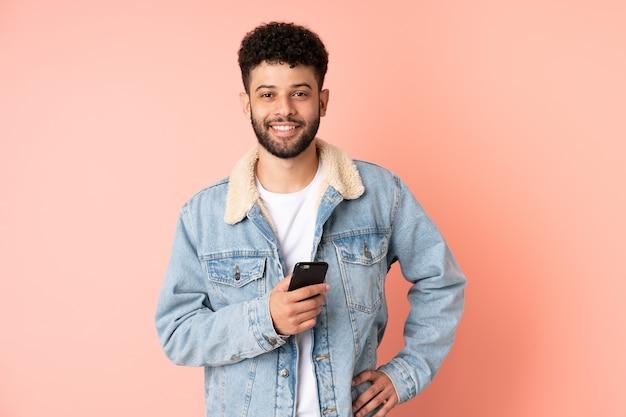 Junger marokkanischer mann, der handy verwendet, lokalisiert auf rosa wand, die mit armen an der hüfte aufwirft und lächelt