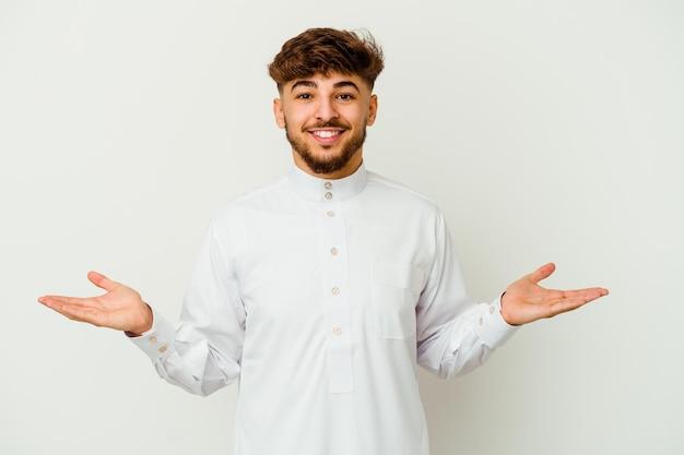 Junger marokkanischer mann, der typische arabische kleidung trägt, lokalisiert auf weiß, das einen willkommenen ausdruck zeigt.