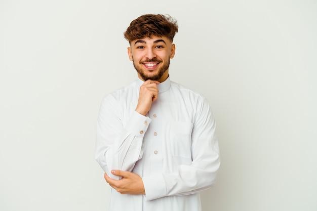 Junger marokkanischer mann, der typische arabische kleidung trägt, lokalisiert auf weiß lächelnd glücklich und zuversichtlich, kinn mit hand berührend.