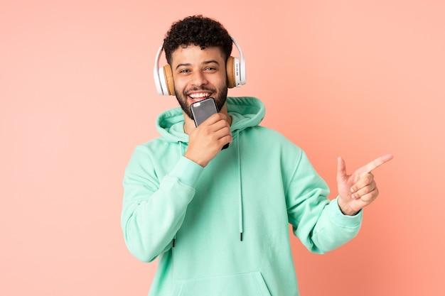 Junger marokkanischer mann lokalisiert auf rosa hintergrund, der musik mit einem handy und gesang hört