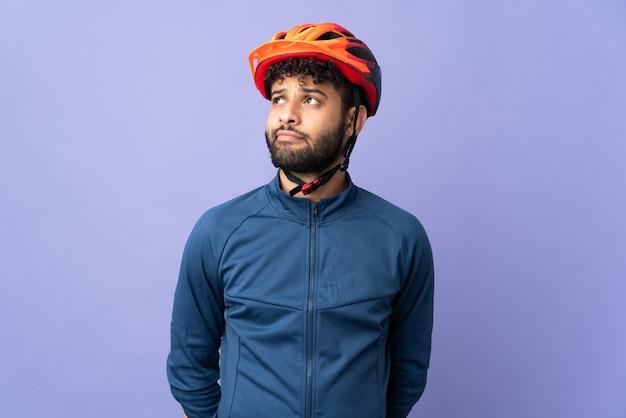 Junger marokkanischer radfahrermann lokalisiert auf lila hintergrund und nach oben schauend