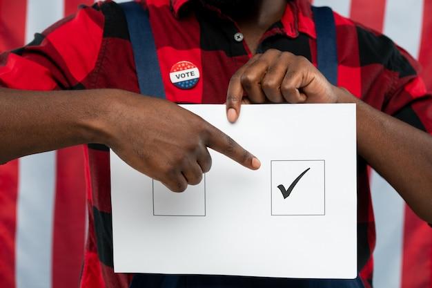 Junger mechaniker, der auf tick in einem der quadrate auf stimmzettel zeigt, während er vor der kamera gegen start-and-stripes-flagge steht