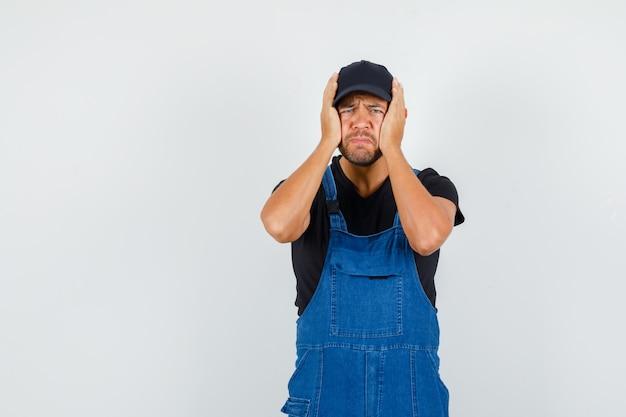 Junger mechaniker, der kopf mit händen in uniform hält und verärgert, vorderansicht schaut.