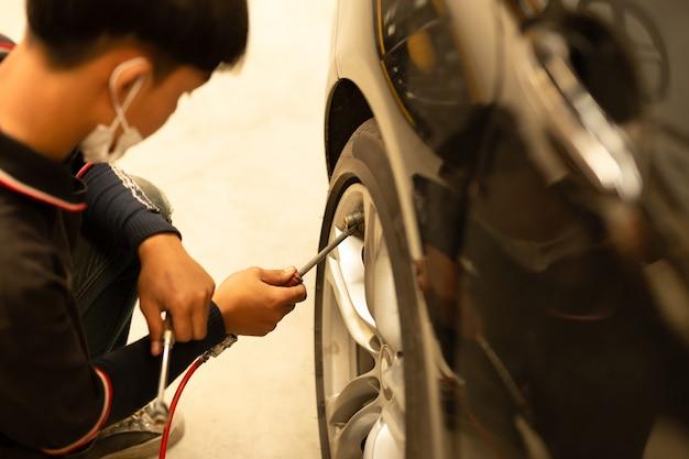 Junger mechaniker, der luftdruck überprüft und luft in den reifen füllt.