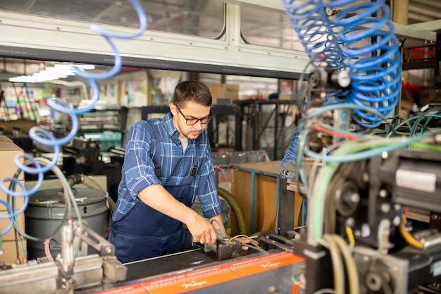 Junger mechaniker der modernen produktionsfabrik, der eine der industriemaschinen untersucht oder repariert