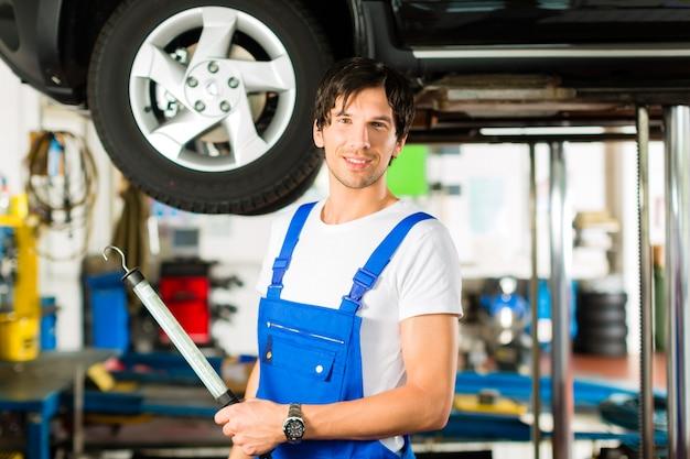 Junger mechaniker im blauen gesamten, der an auto arbeitet