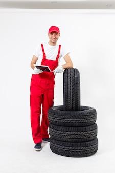 Junger mechaniker in uniform mit einer zwischenablage auf weißem hintergrund