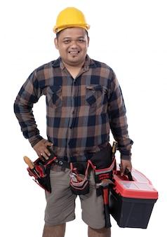 Junger mechaniker mit helm und händen an der taille