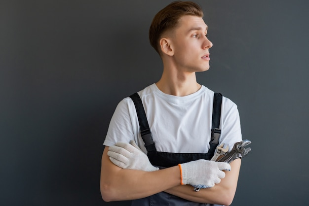 Junger mechaniker mit verschränkten armen und schlüssel, die auf grauem hintergrund stehen