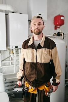 Junger mechaniker mit werkzeuggürtel, der in der toilette des großen hauses steht
