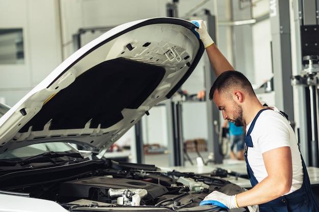 Junger mechanischer mann, der auto überprüft