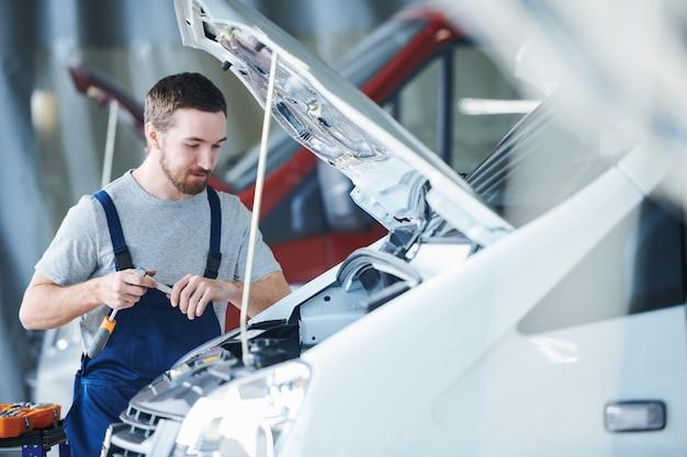Junger meister des autoreparaturdienstes, der motor betrachtet, während er ihn mit speziellem handwerkzeug überprüft