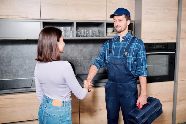 Junger meister des haushaltswartungsdienstes, der nach seiner arbeit die hausfrau verlässt und ihr die hand schüttelt