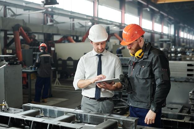 Junger meister im helm und bärtiger ingenieur, der technische skizze auf anzeige des tabletts in der fabrikwerkstatt bespricht