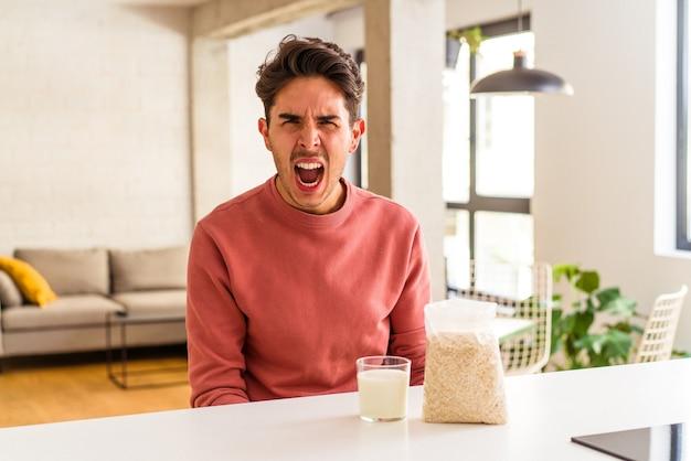 Junger mischling, der in seiner küche haferflocken und milch zum frühstück isst und sehr wütend und aggressiv schreit.