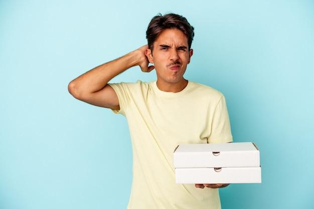 Junger mischlingsmann, der pizzas einzeln auf blauem hintergrund hält, der den hinterkopf berührt, denkt und eine wahl trifft.