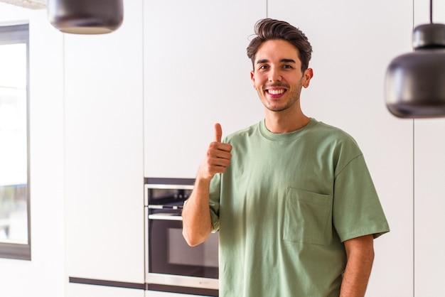 Junger mischlingsmann in seiner küche, der lächelt und daumen hochhebt