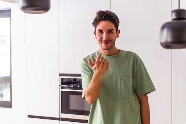 Junger mischlingsmann in seiner küche, der mit dem finger auf sie zeigt, als ob er einladen würde, näher zu kommen.
