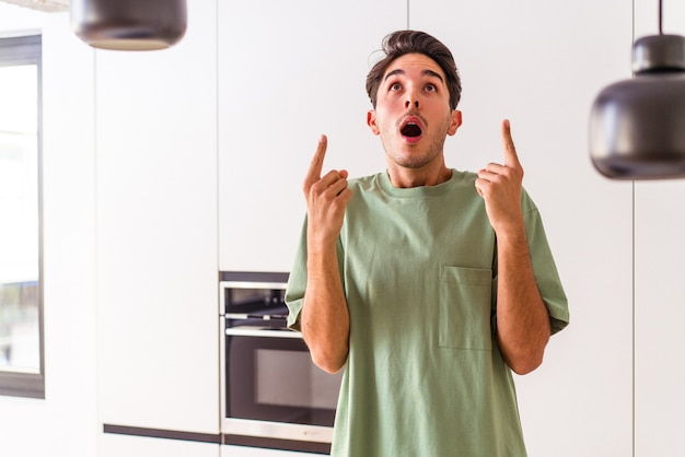 Junger mischlingsmann in seiner küche, der mit geöffnetem mund nach oben zeigt.