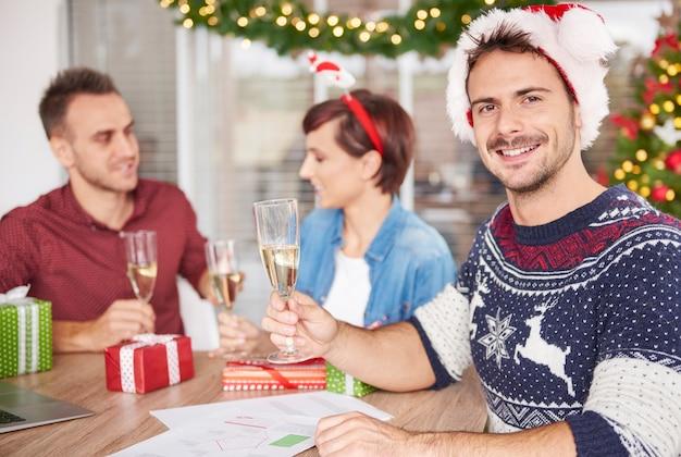 Junger mitarbeiter hält champagner in der hand