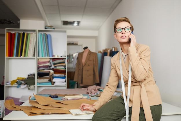 Junger modedesigner, der auf handy spricht, während mit muster in der werkstatt gearbeitet wird